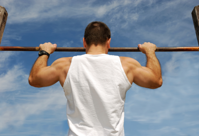 Reaching Goal: Strong Man Doing Pull-ups on a Bar in a Park