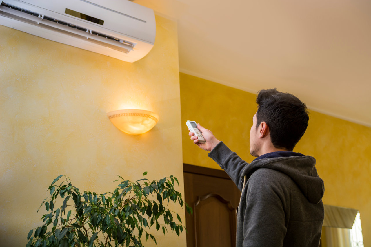 Man-Operating-Air-Conditioner-With-Remote