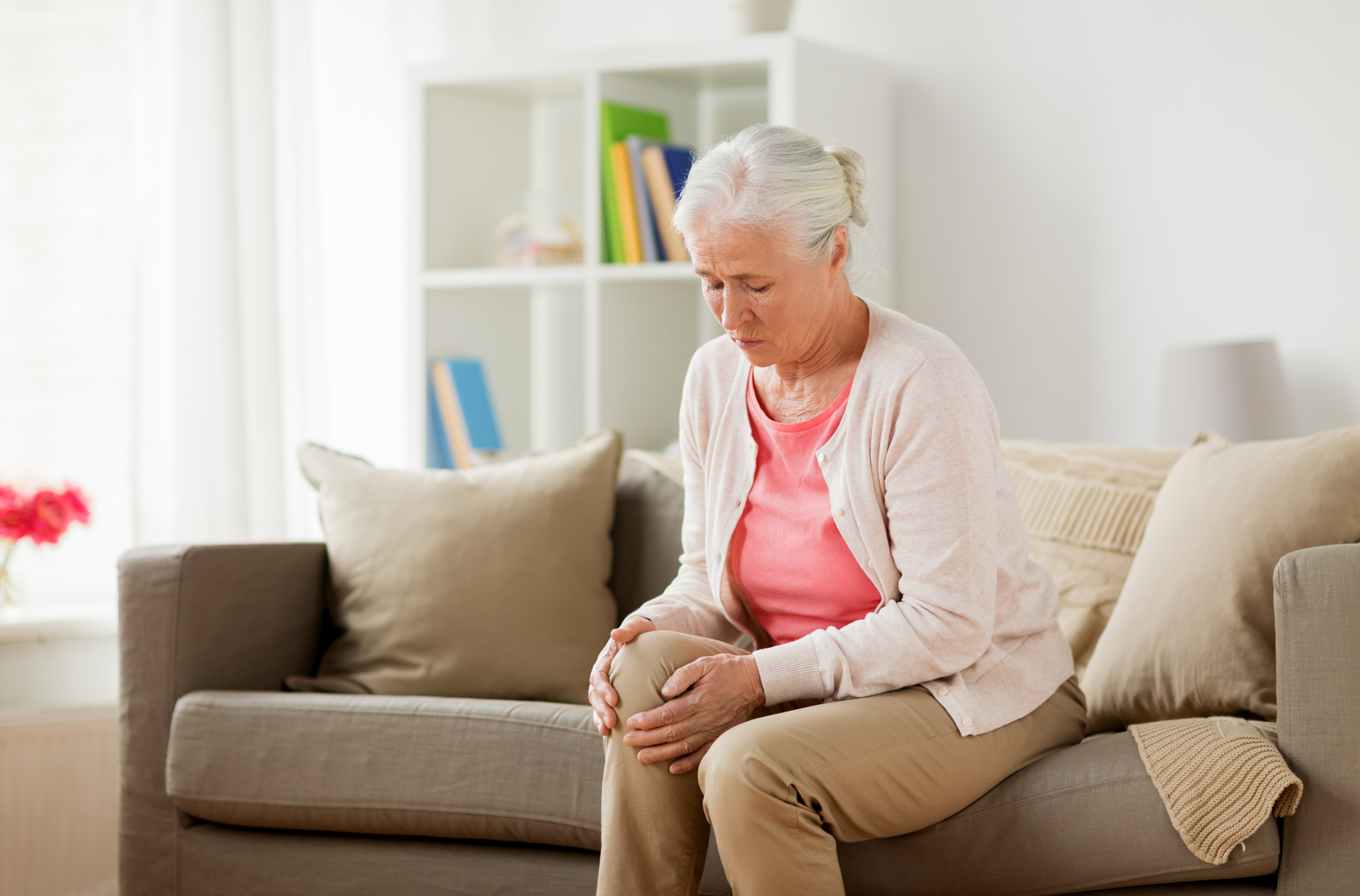 senior woman suffering from pain in leg at home