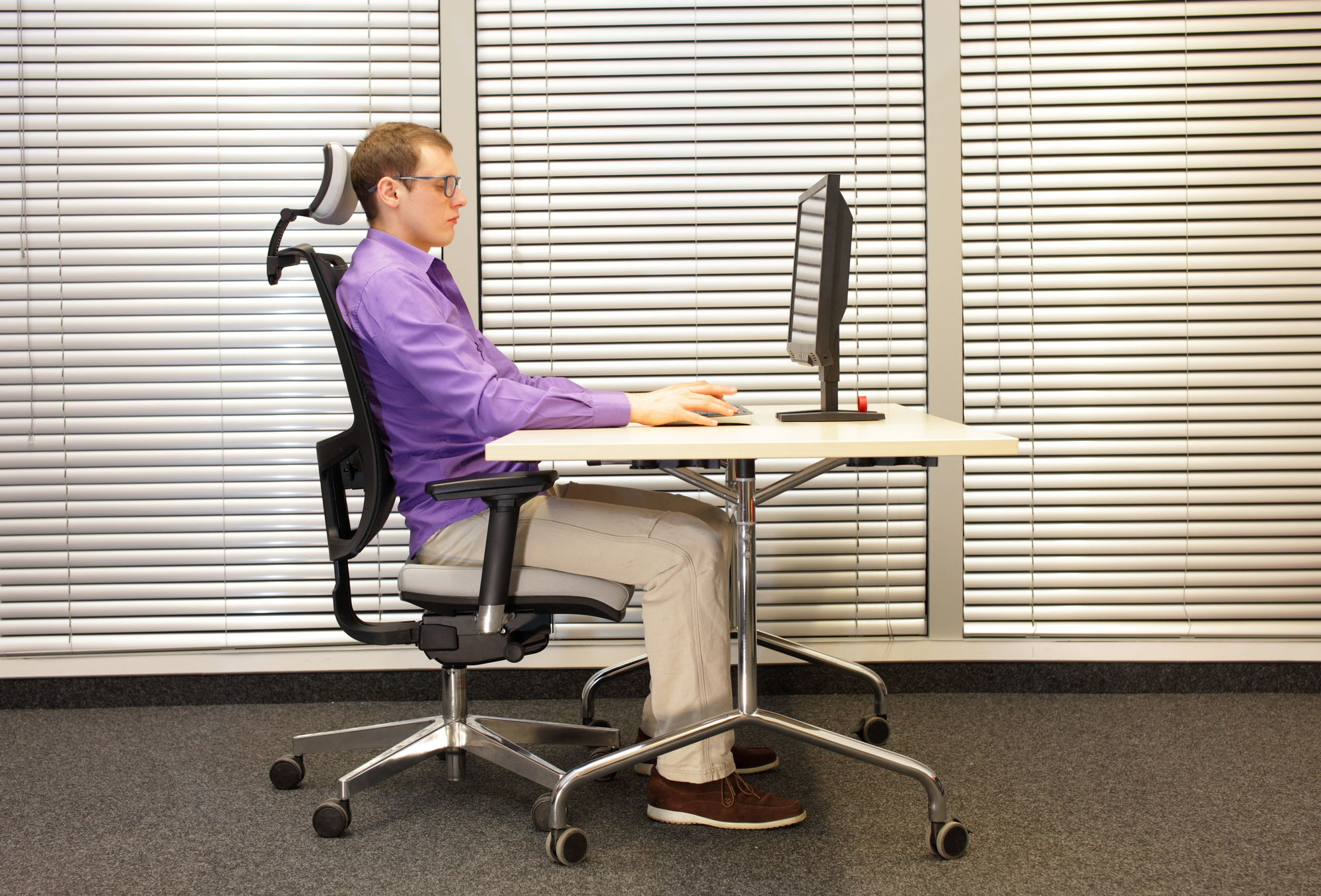 correct sitting position at workstation. man on chair working with pc